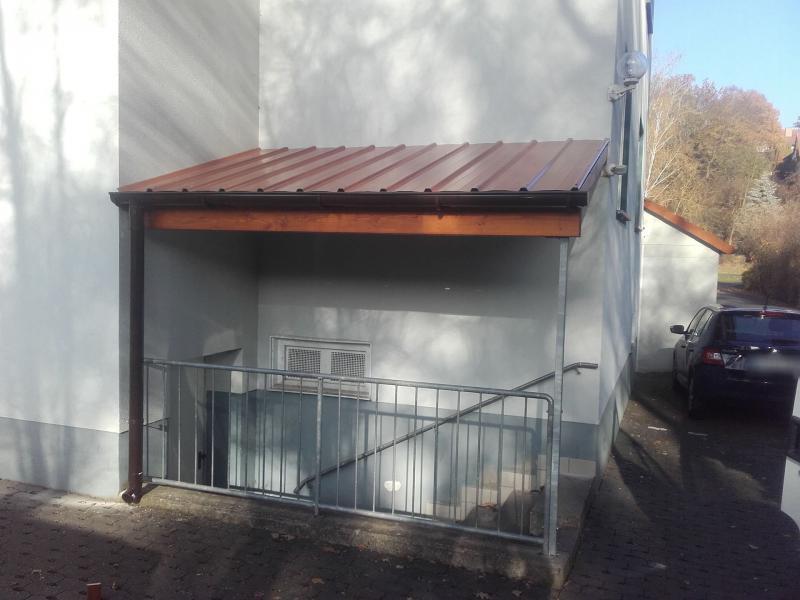 massive Holzkonstruktion mit Blechdach und Dachrinne für einen Kellereingang